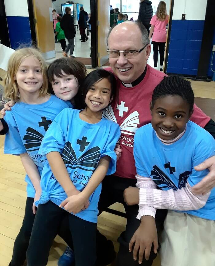 Saint Dennis Parish Father Randy with school children